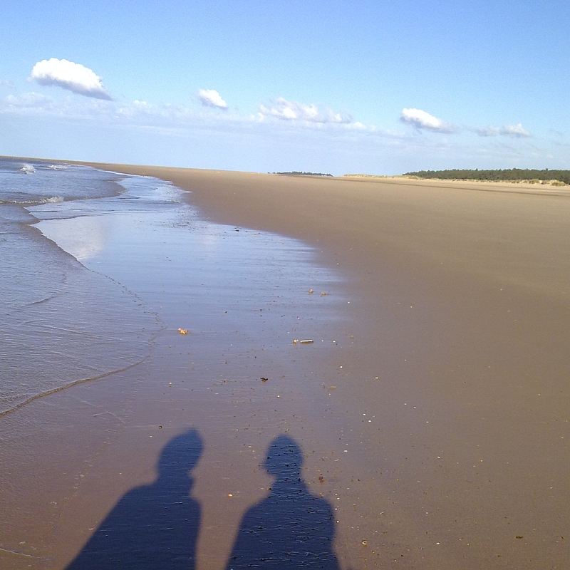 Shadows of two people on Holkham Beach Norfolk by Xtrahead photography