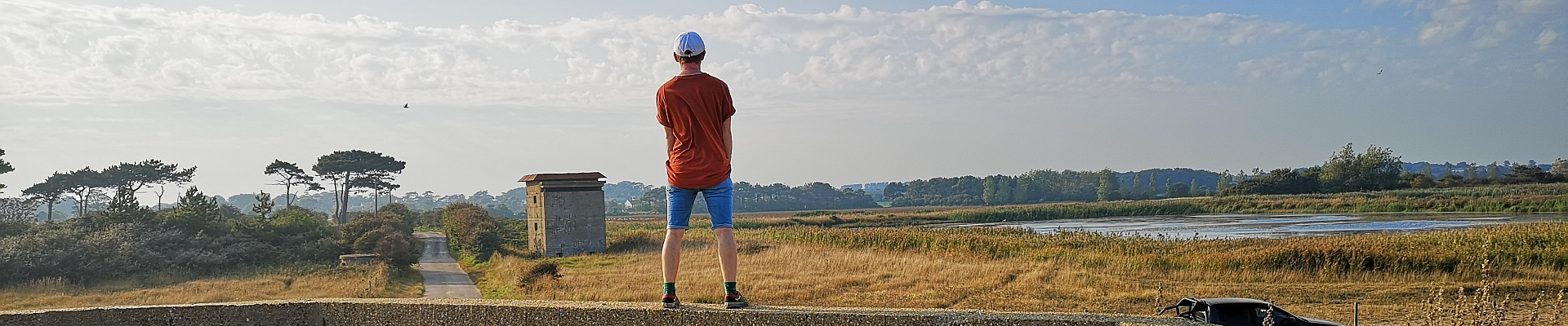 Young man looks inland at lake and Bawdsey landscape Suffolk